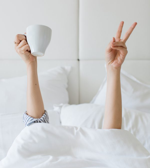Woman under white bed sheets holding coffee. Morning in bed
