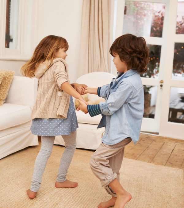 Shot of two young children playing together in the living room at home